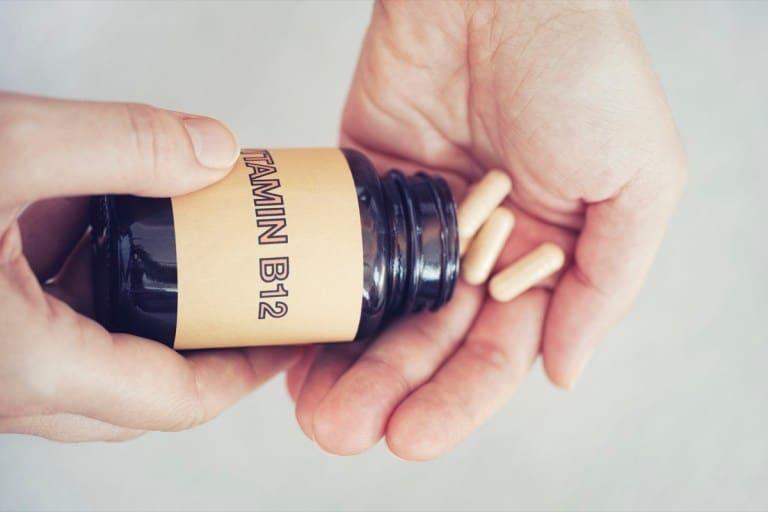 Personne sortant des pilules de vitamine B12 d'une bouteille.